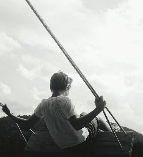 Rear view of boy swinging against sky