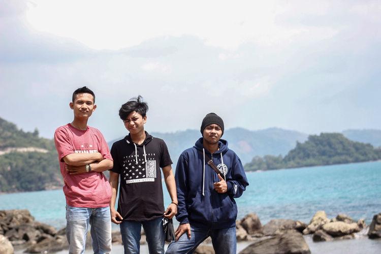 Portrait of friends standing on shore against sky