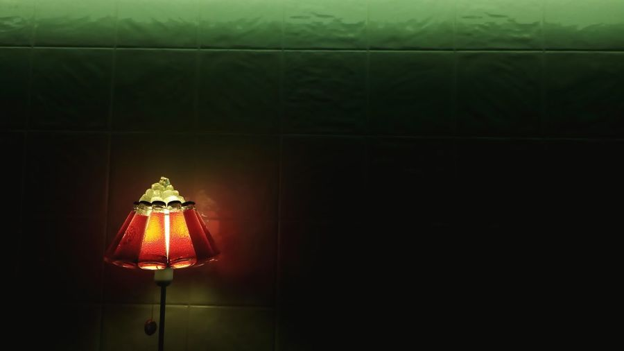 Illuminated lamp against green wall at restaurant