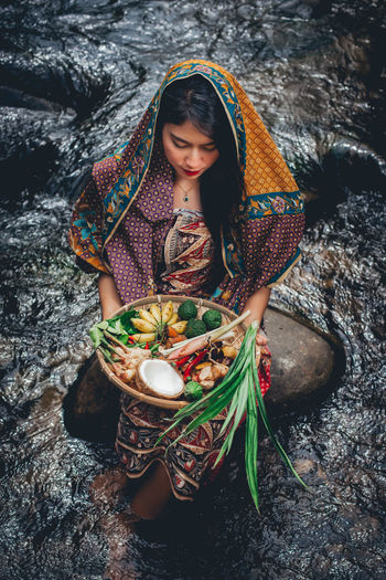 High angle view of woman carrying fruits in basket while standing in river