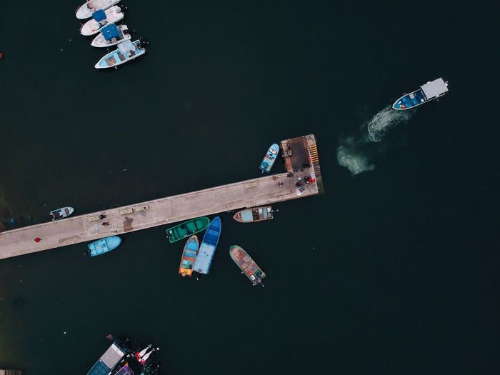 High Angle View Of Boats By Wooden Pier On River