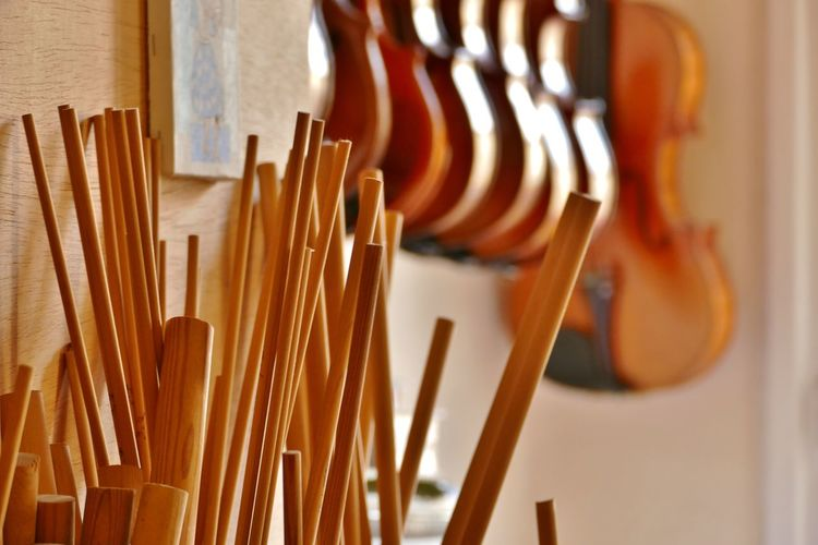 Close-up of wooden sticks with violins in background at store