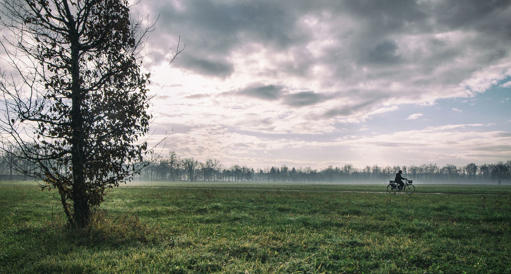 #Moving #bike #movement Beauty In Nature Cloud - Sky Day Field Golf Course Grass Growth Landscape Lifestyles Men Nature One Person Outdoors People Real People Scenics Sky Tranquility Tree