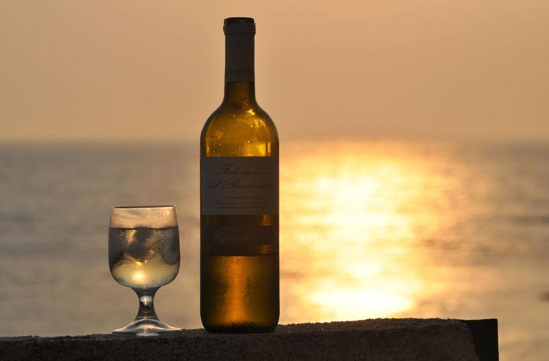 Wine glasses on bottle against sunset sky