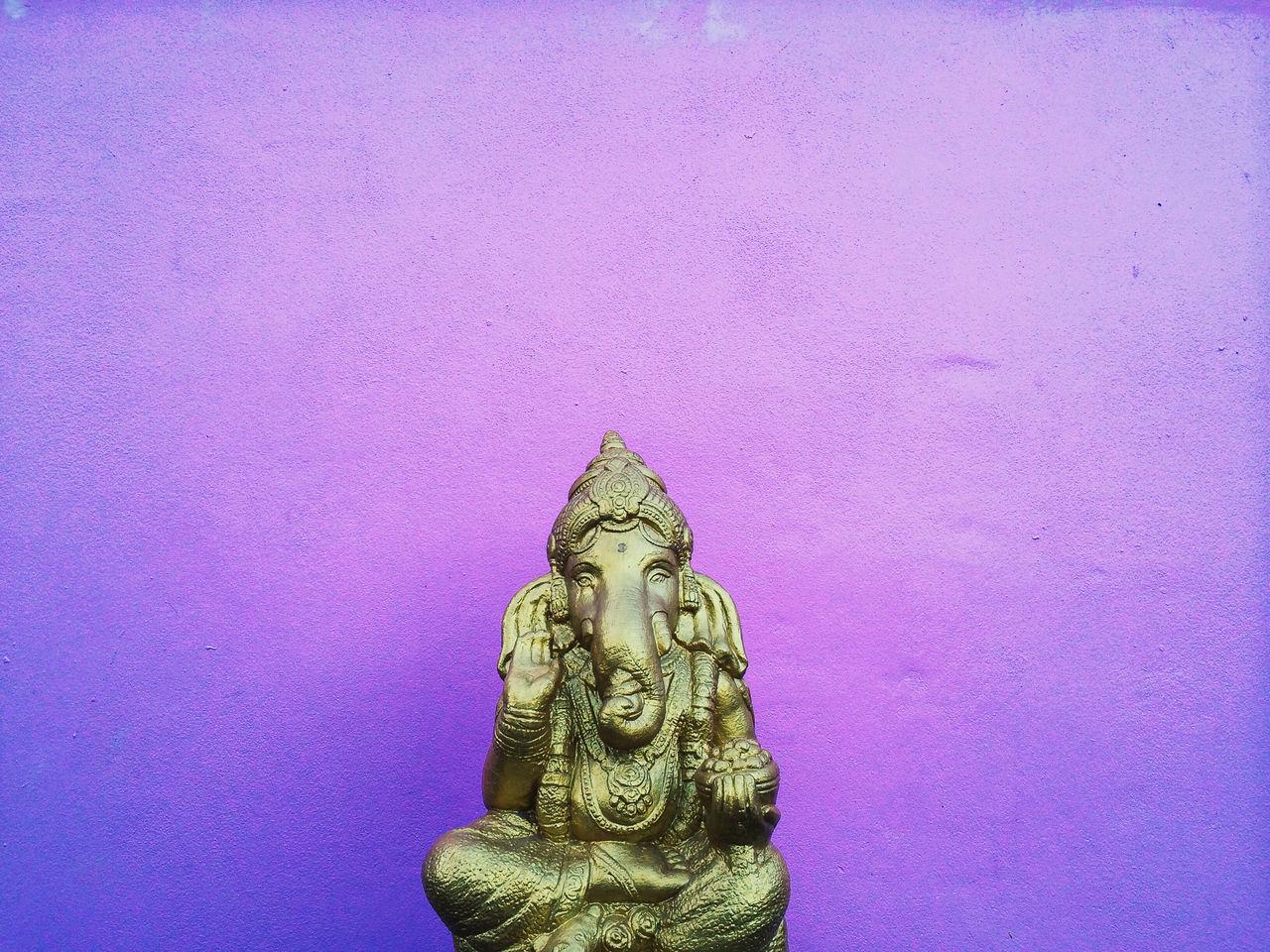 Ganesha Statue Against Purple Against Wall