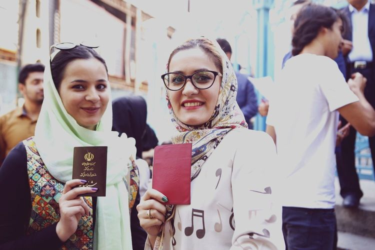 Portrait of smiling young women holding passports while standing outdoors