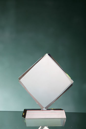 Close-up of illuminated electric lamp on table against wall