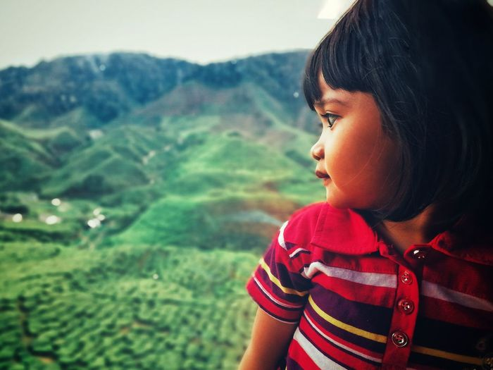 Close-up of cute girl looking at mountains
