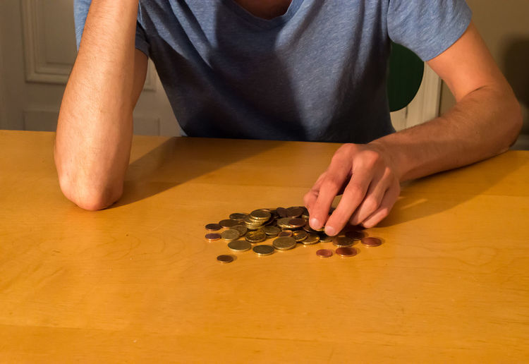 Midsection Of Man Counting Coins On Table At Home