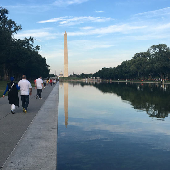 People walking on walkway by canal at washington monument against blue sky