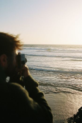 Man photographing sea against sky