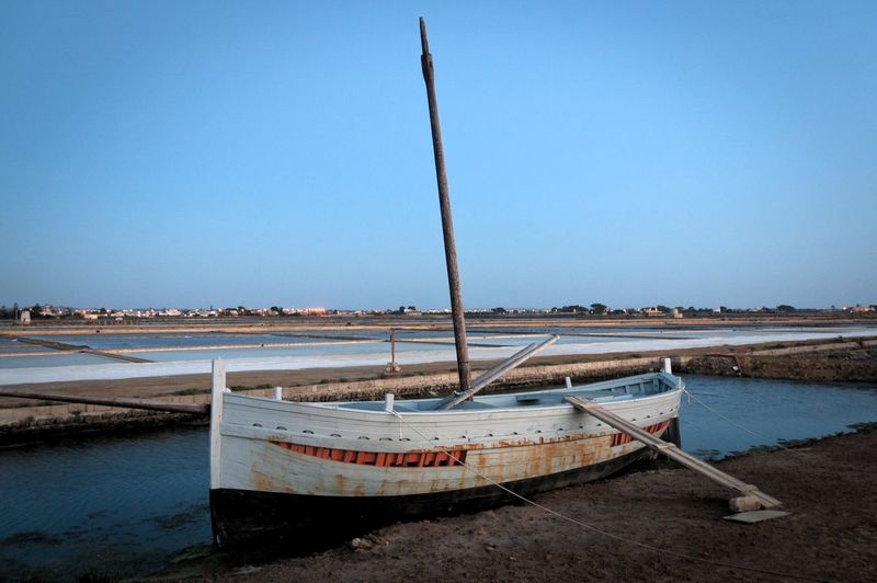 Boat moored at beach against clear blue sky