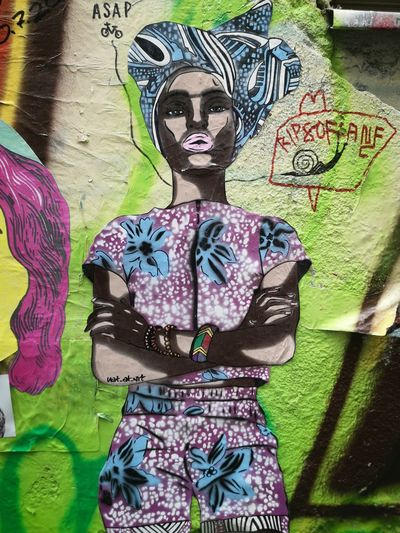Midsection of woman standing against graffiti wall