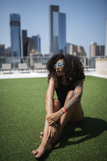 Architecture Building Exterior Built Structure Curly Hair Day Full Length Grass Hair Hairstyle Leisure Activity Lifestyles Nature One Person Outdoors Plant Real People Shadow Sitting Sunlight Women Young Adult