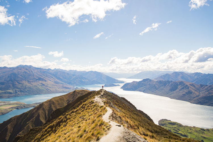 young woman standing at the roys peak lookout point over the lake wanaka on a sunny autumn day Autumn Hiking Wanaka Beauty In Nature Cloud - Sky Day Environment Lake Landscape Mountain Mountain Peak Mountain Range Nature New Zealand Non-urban Scene One Person Outdoors Roys Peak Scenics - Nature Sky Sunlight Tranquil Scene Tranquility Water Young Women The Great Outdoors - 2018 EyeEm Awards Summer Sports Be Brave
