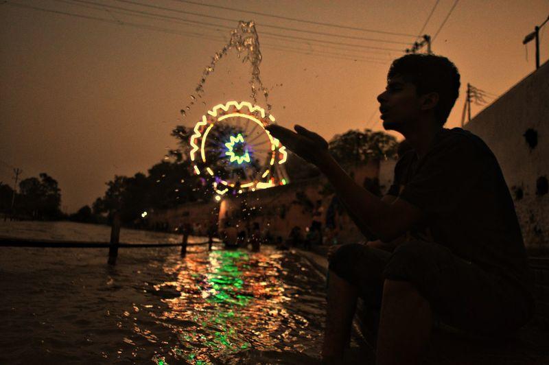 Silhouette boy splashing water at river at night