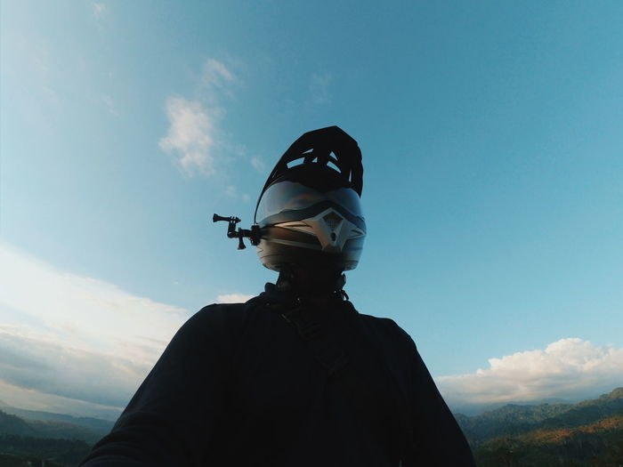 Low angle view of man wearing helmet standing against sky
