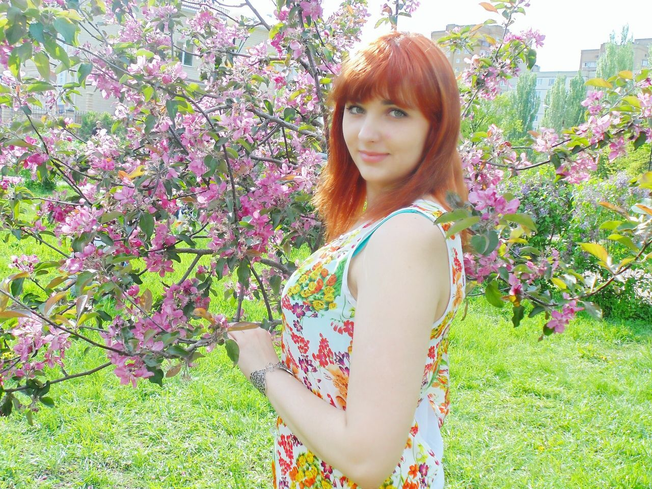 flower, young adult, one person, looking at camera, real people, redhead, young women, tree, growth, standing, beautiful woman, nature, leisure activity, portrait, day, casual clothing, beauty in nature, lifestyles, outdoors, plant, freshness, smiling, medium-length hair