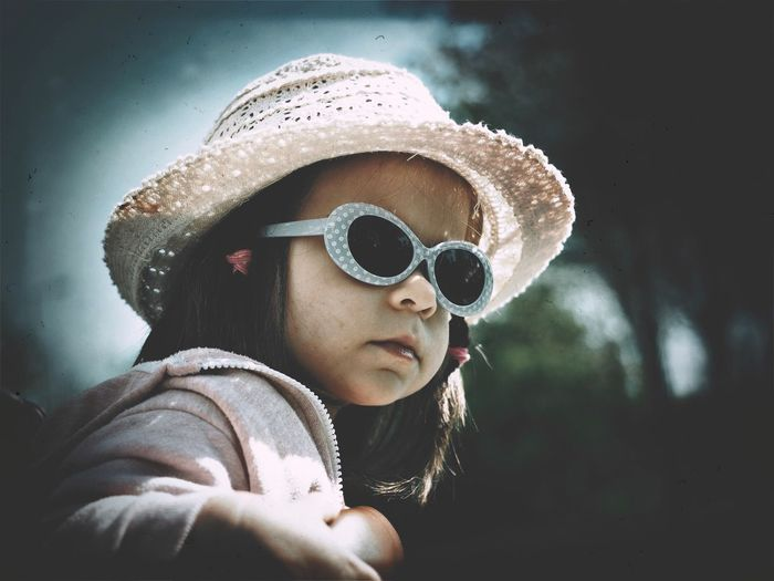Close-up of girl wearing sunglasses and hat on sunny day