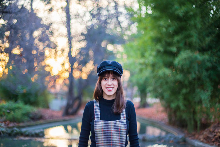 Young woman with stylish clothes posing in a paradisiacal park at sunset Woman Portrait Lake Nature Fashion Girl Female Background Landscape Paradise Hat Young Idyllic Model Autumn One Person Beautiful Happy Caucasian Park Cute Retiro Fall Madrid Stylish