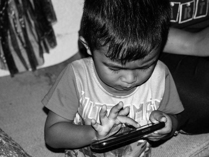Close-Up Of Boy Using Mobile Phone At Home