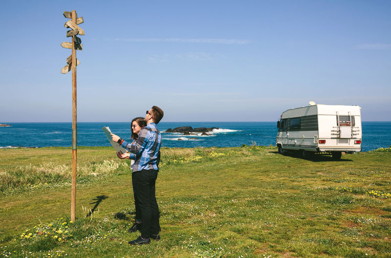 Couple reading sign while holding map on field