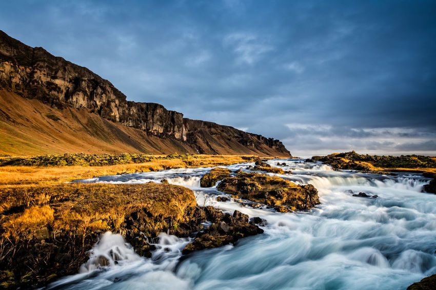 River and waterfall on the Southern Coast of Iceland Flowing Water Iceland Beauty In Nature Cloud - Sky Coast Environment Flowing Flowing Water Land Motion Nature No People Outdoors Real People River Rock - Object Scenics - Nature Sky Water