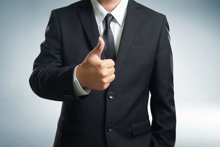 Midsection of businessman gesturing thumbs up against gray background