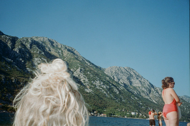 Rear view of woman against mountains against clear sky