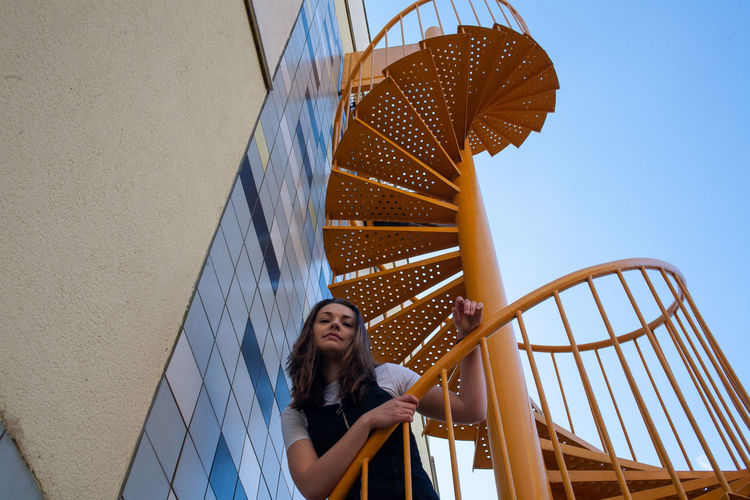 Low angle view of woman looking at staircase