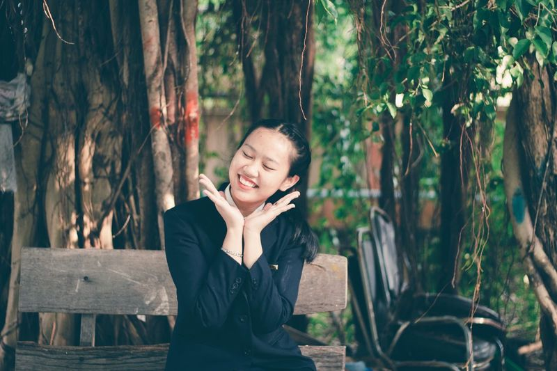 Smiling young woman with eyes closed gesturing in park