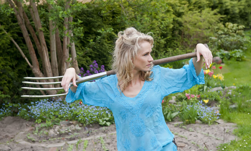 woman with pitchfork Beautiful Elegant Fork Gardening Relaxing Shoulder Standing Stylish Woman Blond Hair Cheerful Day Dreamy Fashionable Garden Graceful Holding Lifestyles Muckrake One Person Pitchfork Sensual_woman Smiling Standing