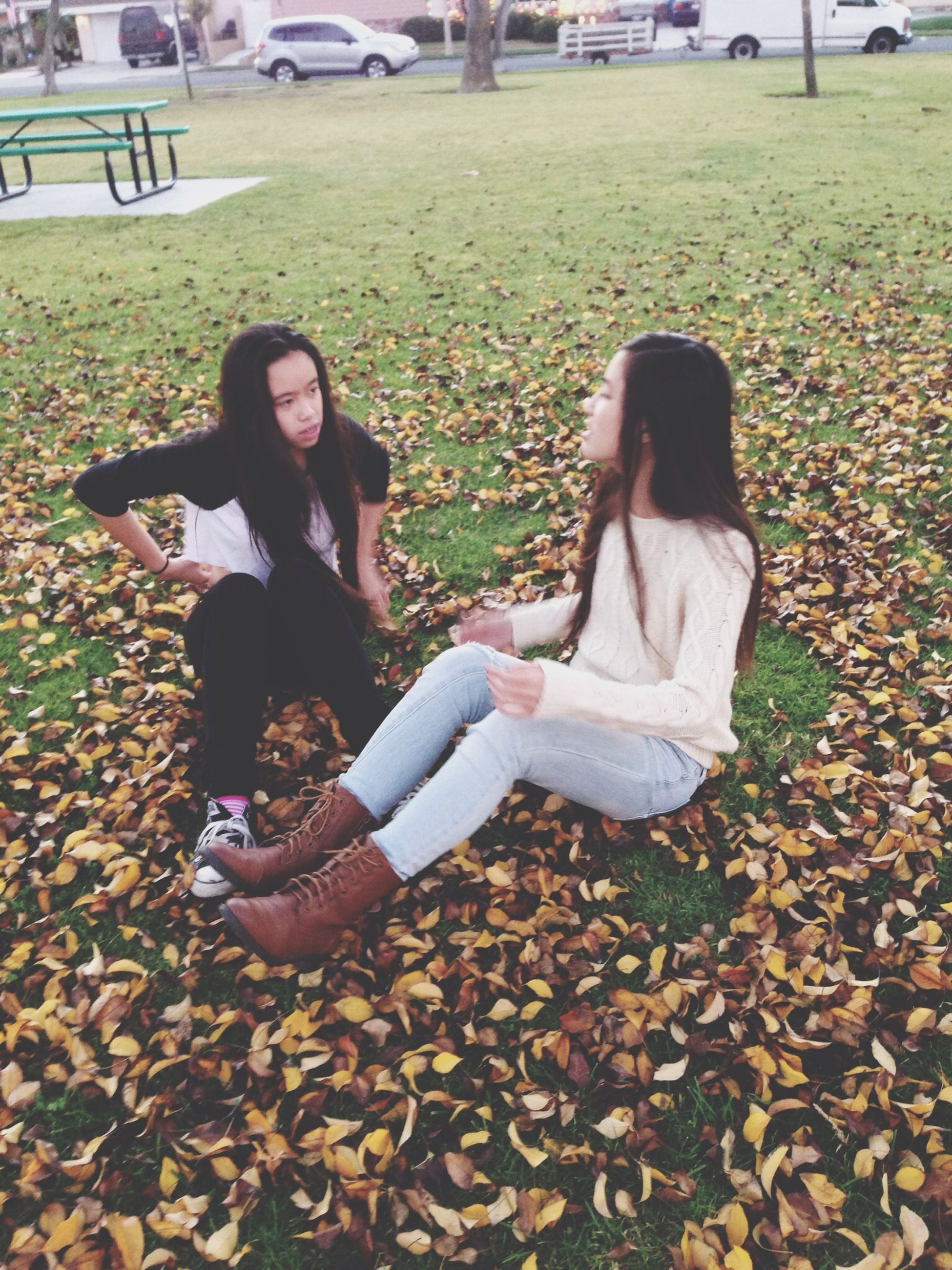 lifestyles, casual clothing, person, leisure activity, full length, childhood, young women, park - man made space, sitting, young adult, elementary age, girls, grass, three quarter length, smiling, field, standing, day