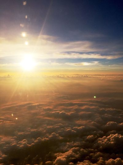 Aerial view of clouds over landscape during sunset