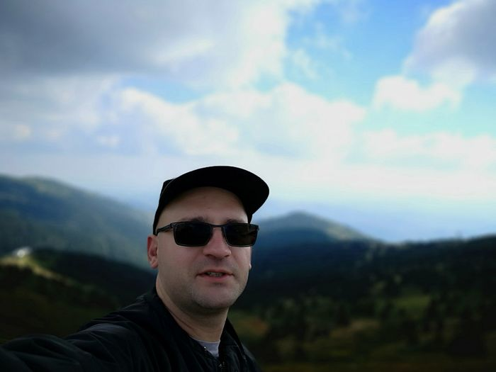 Portrait of mid adult man wearing sunglasses standing on mountain against sky