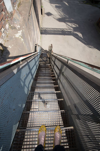 Low section of woman standing on metallic staircase at industrial building