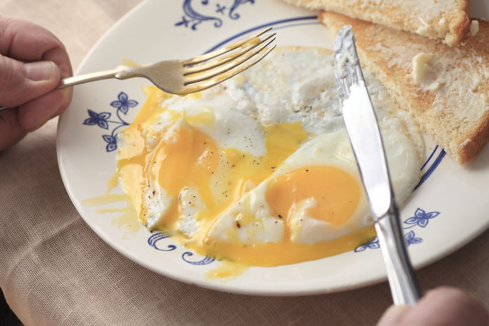 Eating runny fried eggs and toast breakfast Breakfast Buttered Toast Cloth Egg Whites Egg Yolks Fingers Food Hands Indoors  Knife And Fork Man Meal Napkin Natural Light Overhead Phone Camera Plate POV Ready-to-eat Runny Eggs Serving Size Textures