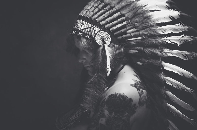 Side View Of Naked Fashion Model Wearing War Bonnet Against Black Background