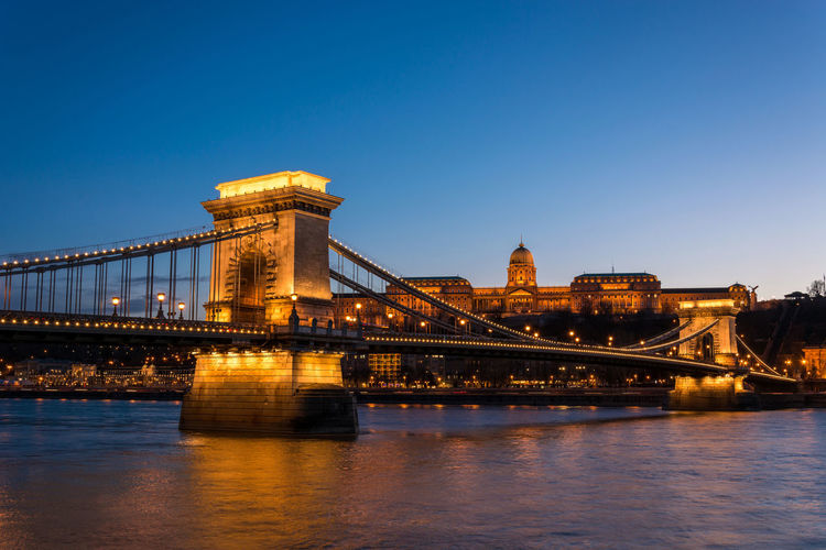 Illuminated chain bridge over danube river against clear blue sky at night