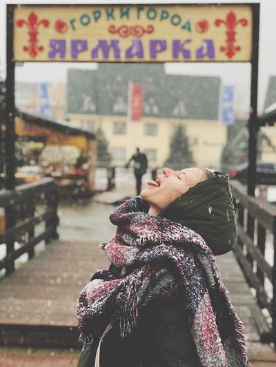 Side View Of Woman With Eyes Closed Sticking Out Tongue During Snowfall