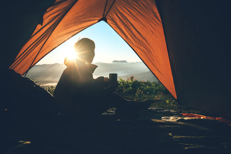 Tent Wireless Technology Outdoors Silhouette Photographing Technology Lens Flare Nature Activity Photography Themes Lifestyles Leisure Activity One Person Sunlight Sunset Orange Color Real People Sky Sun Holding Men