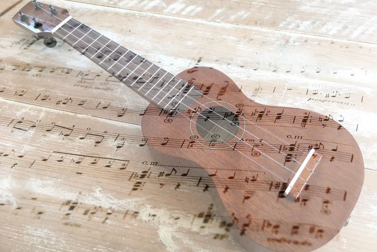 Double exposure of guitar with sheet music