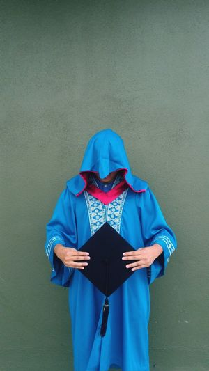 Man Wearing Blue Graduation Gown Holding Black Mortarboard While Standing Against Wall