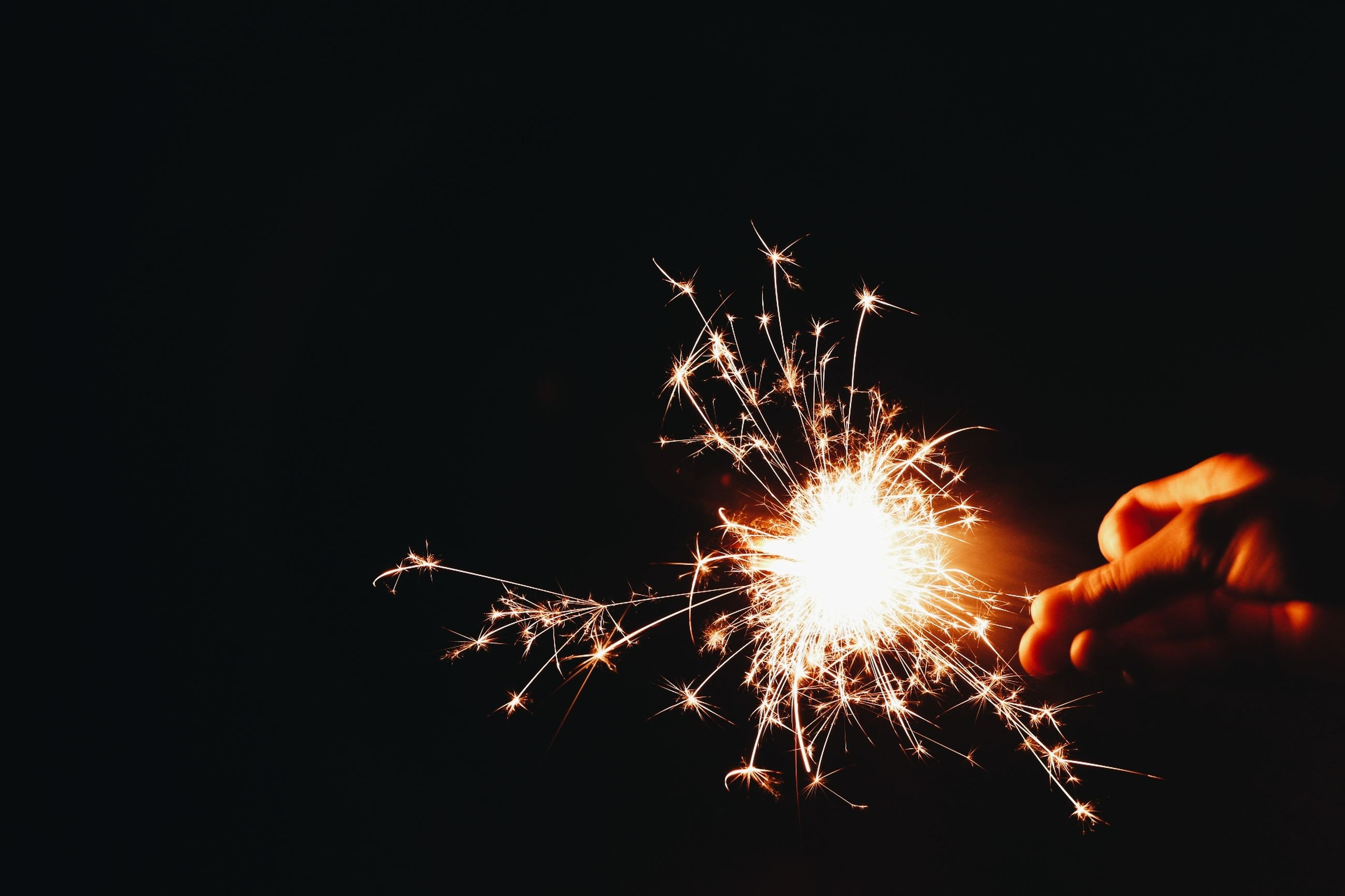 night, human hand, real people, one person, celebration, long exposure, sparks, firework - man made object, leisure activity, holding, sparkler, firework display, human body part, illuminated, black background, outdoors, firework, wire wool, people
