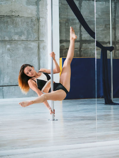 Full length of sensuous woman practicing pole dance in studio