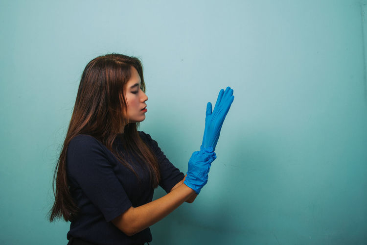 Young woman holding blue while standing against wall