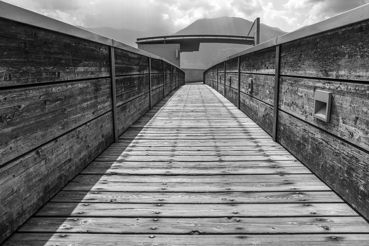 Modern Walkway in Wood and Mountain in Switzerland. Modern Architecture Black And White Bridge Bridge - Man Made Structure Building Exterior Built Structure Connection Day Design Diminishing Perspective Direction Footbridge Footpath Long Mountain No People Outdoors Railing Sky Swiss Alps Swiss Culture The Way Forward Transportation Wall