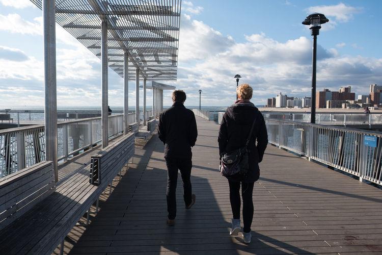 Two men walking outside along a wooden boardwalk on the Coney Island pier in Brooklyn New York. Sunny day in Coney Island, Boardwalk Boardwalks Brooklyn Brooklyn New York Brooklyn NewYork Brooklyn Ny Brooklyn Nyc Coney Island Coney Island / Brooklyn NY Coney Island Beach Coney Island Boardwalk Coney Island Pier