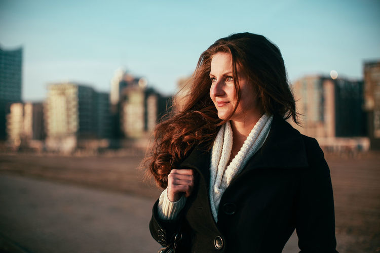 Portrait of woman looking at city against sky at hafencity hamburg
