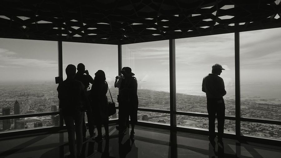 Silhouette People Looking Through Window From Burj Khalifa